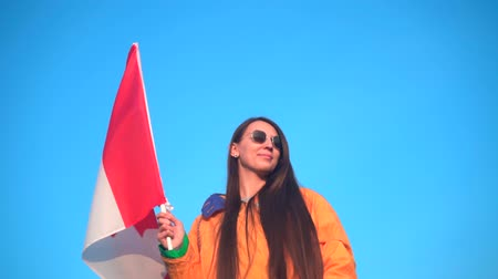 tramp : A young girl in a yellow jacket, gray pants and glasses holds in her hand the flag of Canada. In the background are hills and sky. The flag of Canada is developing in the wind. Stock Footage