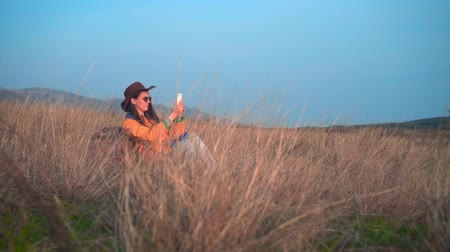 realizar : A young girl with long dark hair in a yellow jacket, a leather cowboy hat and glasses is sitting in the grass, leaning on a tourist backpack and making a photo on the phone. Background mountains, sky.
