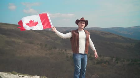frizura : A man in a hat, vest and leather jacket and jeans is holding a Canadian flag against the backdrop of mountains, woods and the sky. Flag of Canada develops in the wind. Stock mozgókép