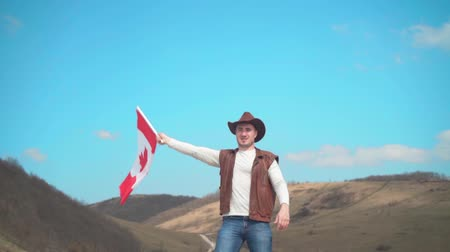 головной убор : A man in a hat, vest and leather jacket and jeans is waving the Canadian flag against the backdrop of mountains, woods and the sky. Flag of Canada develops in the wind. Стоковые видеозаписи