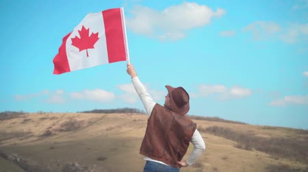 головной убор : A man in a hat, vest and leather jacket and jeans holds a Canadian flag against the backdrop of mountains, forests and sky. A man stands with his back in the frame. Стоковые видеозаписи
