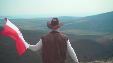 frizura : A man in a hat, vest and leather jacket and jeans holds a Canadian flag against the backdrop of mountains, forests and sky. A man stands with his back in the frame. Stock mozgókép