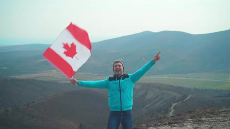 canadense : A young man in a blue sweater and hat holds the Canadian flag in his hand. A person experiences happiness and a sense of pride. He stands against the backdrop of mountains and sky.