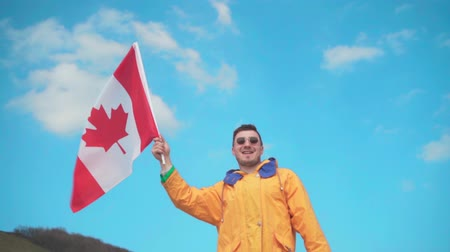 canadense : A young man in a yellow jacket, blue jeans and glasses is standing in the mountains, holding the flag of Canada, smiling and showing a super sign. Behind the backdrop of the mountains and the sky. Stock Footage
