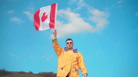 canadense : A young man in a yellow jacket, blue jeans and glasses stands in the mountains and waves the flag of Canada from side to side. Behind the backdrop of the mountains and the sky.