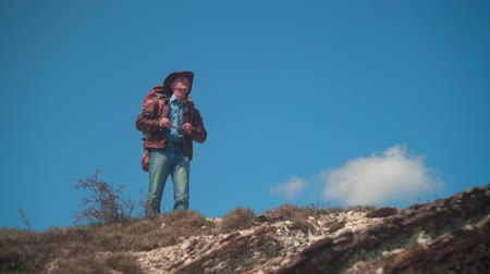 frizura : In the mountains, a man in a cowboy hat, leather jacket, blue jeans, a large tourist backpack on his shoulders. The man looks around, taking off his glasses and looking at him.