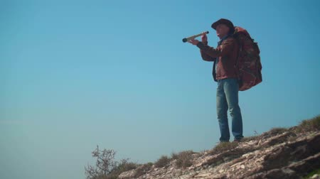 frizura : In the mountains there is a man in a cowboy hat, leather jacket, blue jeans, a large tourist backpack on his shoulders. A man looks through a telescope. Background of mountains and sky.
