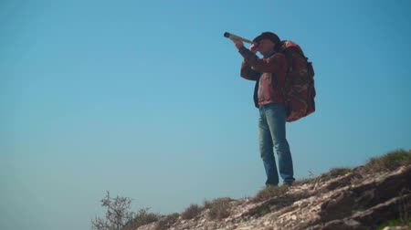 головной убор : In the mountains there is a man in a cowboy hat, leather jacket, blue jeans, a large tourist backpack on his shoulders. A man looks through a telescope. Background of mountains and sky.
