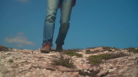 epik : In the mountains, a man in a cowboy hat, leather jacket, blue jeans with a large tourist backpack. A man approaches, takes off his backpack and sets it on the ground. Background of mountains and sky. Stok Video
