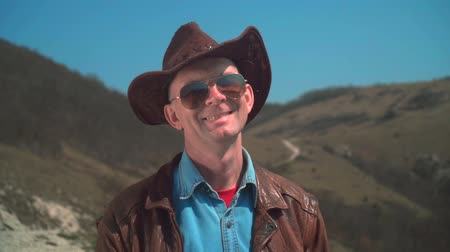 frizura : In the mountains there is a man in a cowboy hat, leather jacket, glasses. The man looks at the frame and smiles. Background of mountains and sky.