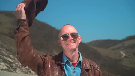 frizura : In the mountains there is a man in a cowboy hat, leather jacket, glasses. A man puts his hand to his hat and takes off his hat. Background of mountains and sky.