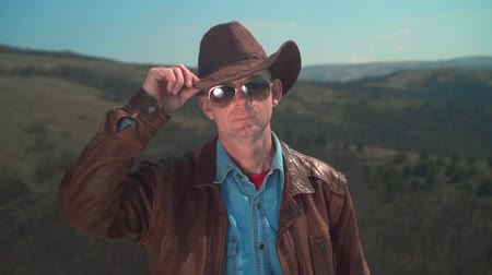 frizura : In the mountains, a man in a cowboy hat, leather jacket, glasses. A man touches his hat with his hand, showing a sign of greeting. Background of mountains and sky. Stock mozgókép