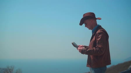 frizura : A man in a cowboy hat, leather jacket, blue jeans and glasses is standing in the mountains and considering a traveler map. Background of mountains and sky.
