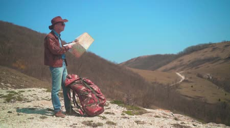 головной убор : A man in a cowboy hat, leather jacket, blue jeans and glasses is standing in the mountains and considering a traveler map. Background of mountains and sky.