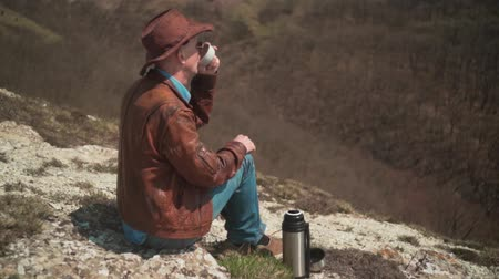 frizura : In the mountains sits a man in a cowboy hat, leather jacket, blue jeans and glasses. A man drinking tea from a thermos. Background of mountains and sky. Stock mozgókép