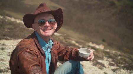 frizura : In the mountains sits a man in a cowboy hat, leather jacket, blue jeans and glasses. The man looks at the frame and smiles. Background of mountains and sky.