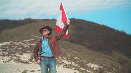 головной убор : A man in a hat and sunglasses, leather jacket and jeans holding a Canadian flag on the background of mountains, woods and the sky. Flag of Canada develops in the wind.