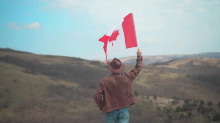 canadense : A man in a hat and sunglasses, a leather jacket and jeans holding a Canadian flag against the backdrop of mountains, forests and the sky. A man stands with his back in the frame.