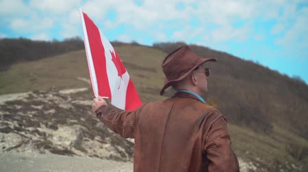 vaqueiro : A man in a hat and sunglasses, a leather jacket and jeans holding a Canadian flag against the backdrop of mountains, forests and the sky. A man stands with his back in the frame.