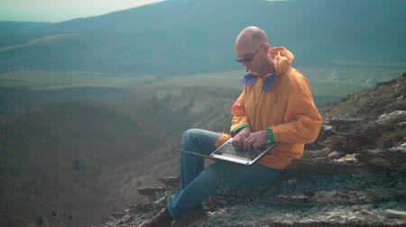 landloper : A man in a yellow jacket, blue jeans and glasses sits on the edge of a cliff and works on a laptop, he looks at the screen and types the text. In the background are hills and sky. Mountain landscape.