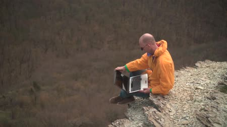 dağcı : A man in a yellow jacket, blue jeans and glasses sits on the edge of a cliff opens a laptop and starts working. In the background are hills and woods. Mountain landscape.
