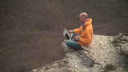 realizar : A man in a yellow jacket, blue jeans and glasses sits on the edge of a cliff and works on a laptop, he looks at the screen and types the text. In the background hills and woods. Mountain landscape.
