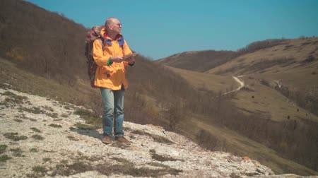 vezetett : A man in a yellow jacket and glasses stands in the mountains, enjoying the scenery and is guided by the map. In the background are hills and sky. Mountain landscape.