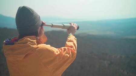 realizar : A young girl with long dark hair in a yellow jacket and a gray cap is standing in the mountains and looking through a telescope. Background mountains, sky.