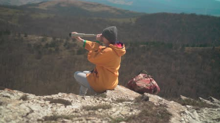 landloper : A young girl with long dark hair in a yellow jacket and a gray cap is standing in the mountains and looking through a telescope. Background mountains, sky.