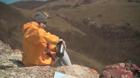 realizar : A young girl with long dark hair in a yellow jacket, a gray cap and glasses sits on a mountain, pours tea from a thermos, then drinks. Background mountains, sky.