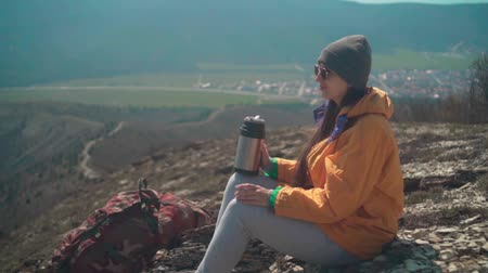альпинист : A young girl with long dark hair in a yellow jacket, a gray cap and glasses sits on the mountain and drinks tea. Background mountains, sky.
