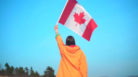 canadense : A young girl in a yellow jacket, gray pants and glasses holds in her hand the flag of Canada. The flag of Canada is developing in the wind. The girl is standing back in the frame. Stock Footage