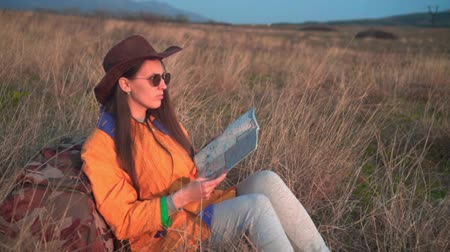 backpacken : A young girl with long dark hair in a yellow jacket, a leather cowboy hat and glasses sits in the same grass, leaning on a tourist backpack, looking at the traveler s map. Background mountains, sky.