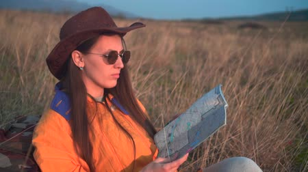 realizar : A young girl with long dark hair in a yellow jacket, a leather cowboy hat and glasses sits in the same grass, leaning on a tourist backpack, looking at the traveler s map. Background mountains, sky.