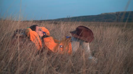 head over : A young girl with long dark hair in a yellow jacket and glasses is lying in the yellow grass, leaning on a tourist backpack, her arms are thrown back over her head, and a leather cowboy hat on knee. Stock Footage