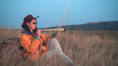 realizar : A young girl with long dark hair in a yellow jacket and a leather cowboy hat sits in the grass, leaning on a tourist backpack and looking through a telescope. Background mountains, sky.