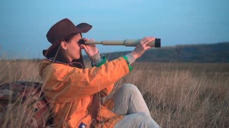 tramp : A young girl with long dark hair in a yellow jacket and a leather cowboy hat sits in the grass, leaning on a tourist backpack and looking through a telescope. Background mountains, sky.