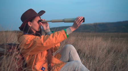 landloper : A young girl with long dark hair in a yellow jacket and a leather cowboy hat sits in the grass, leaning on a tourist backpack and looking through a telescope. Background mountains, sky.