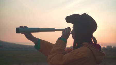 realizar : A young girl with long dark hair in a yellow jacket and a leather cowboy hat looks into a telescope. Background mountains, sky, sea and city.