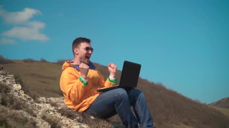work at height : A young man in a yellow jacket, blue jeans and glasses sits in the mountains, enjoys the scenery, works at a laptop and rejoices, emotions of joy. In the background are hills and sky. Mountain. Stock Footage