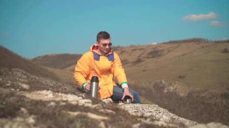 landloper : A young man in a yellow jacket, blue jeans and glasses sits in the mountains, enjoys the scenery and drinks tea from a thermos. In the background are hills and sky. Mountain landscape.