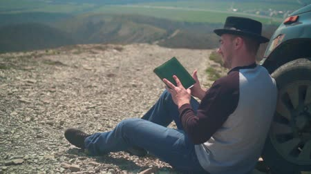 magasság : A young man in a sweater, blue jeans and a black hat sits leaning on the wheel of a car and reads a book. In the background are hills and sky.