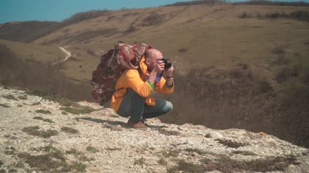 realizar : A man in a yellow jacket and glasses is standing in the mountains, enjoying the scenery and making photos on dslr camera. In the background are hills and sky. Mountain landscape.