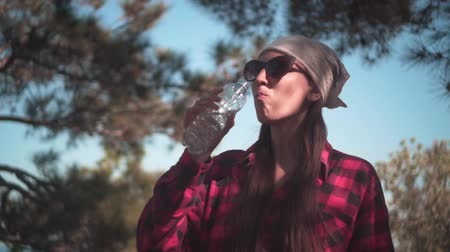 backpacken : A girl with dark hair in a black and red shirt, a bandana and glasses stands in the forest and drinks water from a plastic bottle. Sky background, forest.