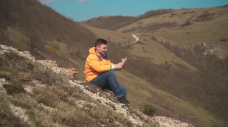 альпинист : A young man in a yellow jacket, blue jeans sits on a rock and looks into the distance, putting a hand to his head, holding a traveler s card in his other hand.