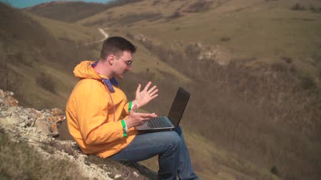 tramp : A young man in a yellow jacket, blue jeans and glasses sits in the mountains, works for a laptop, is nervous, swears, shouts, negative. In the background are hills and sky. Stock Footage
