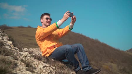 magasság : A young man in a yellow jacket, blue jeans and glasses sits in the mountains, enjoys the scenery, shoots video on the phone. In the background are hills and sky. Mountain landscape.