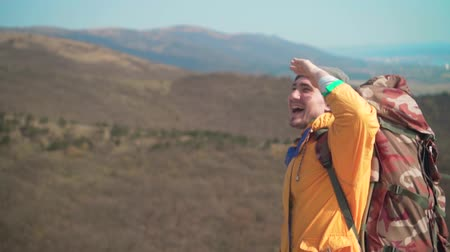 barbone : A young man in a yellow jacket, blue jeans and a hat with a large tourist backpack is standing on the mountain and looking to the side, smiling, emotions of delight. Background of mountains and sky.