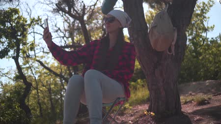 tırmanıcı : A girl with dark hair in a black and red shirt, a bandana and glasses sits in the forest, takes a selfie on the phone, a tourist backpack hangs on a tree. Background sky, forest. Stok Video