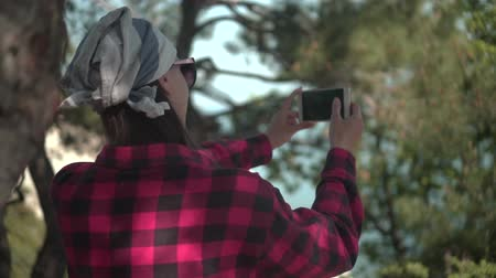 góral : A girl with dark hair in a black and red shirt, a bandana and glasses stands between the trees, makes a photo on the phone. Background mountains, sky.